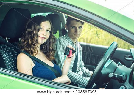 Instructor Gives The Beginner The Car Key. Woman Taking An Exam At The Driving School
