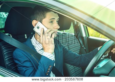 Man Driver Talking On A Phone In The Car. Distracted And Dangerous Driving. The Traffic Violation.