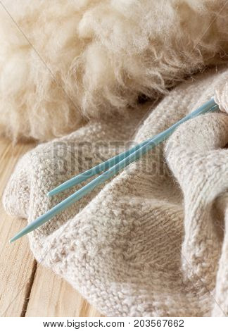 knitted fabric made of natural wool knitting needles and wool on old wooden background