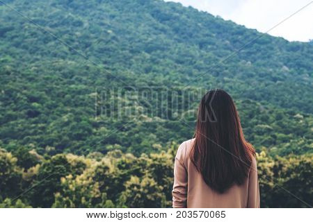 A woman turn back and standing with blue sky green nature and mountain background
