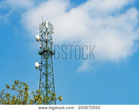 Green tower with microwave link and TV transmitter antennas telecommunication mast antennas wireless technology over blue sky.