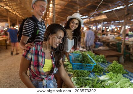 Group Of People Choosing Potherbs On Street Market Happy Smiling Friends Buy Products Together Shopping On Asian Bazaar
