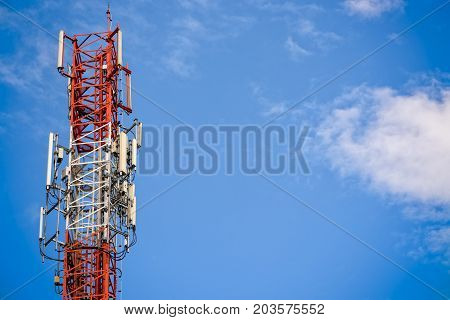 Telecommunications antenna mobile phone signal tower on blue sky background in Thailand