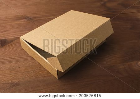 Cardboard box on a dark wooden background. Corrugated cardboard