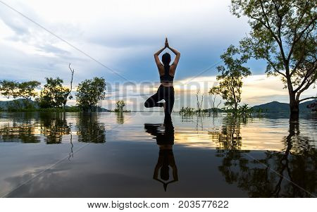 Silhouette young woman lifestyle exercising vital meditate and practicing reflect on Flood the trees in the reservoir background sunset. Healthy Concept.