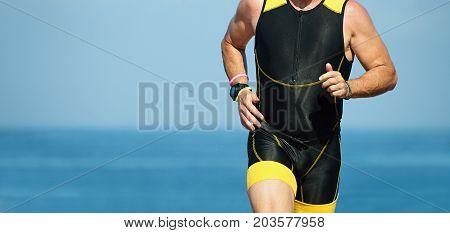 Man runner running on triathlon race on sunny days at ocean