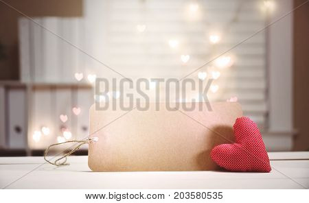 Heart cushion with card on heart shaped light background