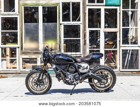 Cool custom made scrambler style cafe racer with standing in front of a glass house
