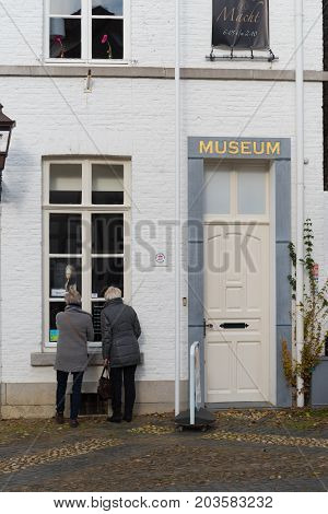 THORN NETHERLANDS - NOVEMBER 6 2016: Two unknown elderly women looking through a museum window in the white village of Thorn