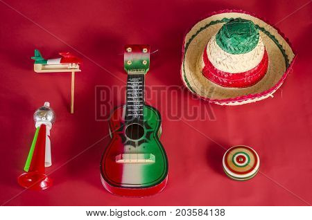 Yo yo,guitar,toy trumpet and noisemaker against red background. Accessories for mexican Independence Day celebration