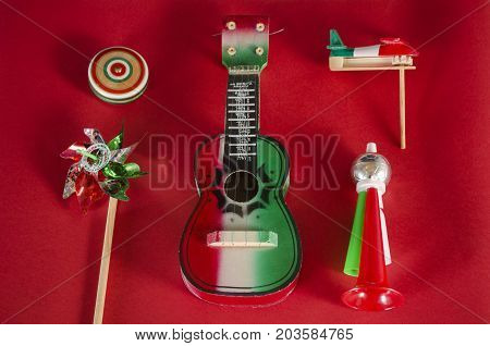 Yo yo,toy windmill,guitar,toy trumpet and noisemaker against red background. Accessories for mexican Independence Day celebration