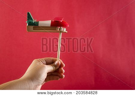 Hand holding a noisemaker against red background