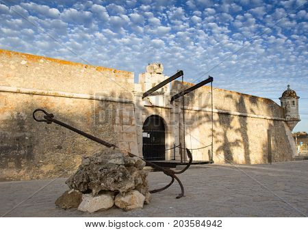 Old fortification of the city of Lagos Algarve Portugal. Big old rusy anchor. Evening picture with blue sky and small clouds. The place of overseas discoveries.