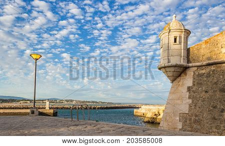 Old fortification of the city of Lagos Algarve Portugal. Evening picture with blue sky and small clouds. The place of overseas discoveries.