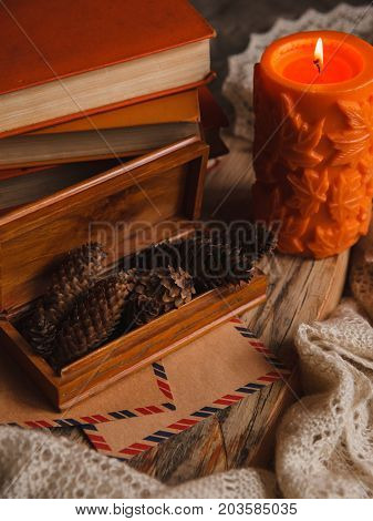 Autumn Cozy Still Life Of Big Orange Candle, Pile Of Books And Box Of Pine Bumps.