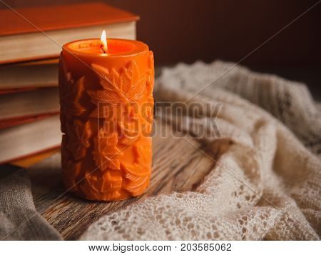 Autumn Cozy Still Life Of Big Orange Candle And Pile Of Books With Warm Downy Shawl.
