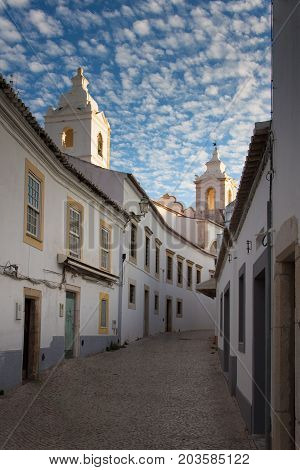 The narrow lane leading to the church of Saint Anthony. Lagos Algarve Portugal. Summer picture with blue sky and little white clouds.