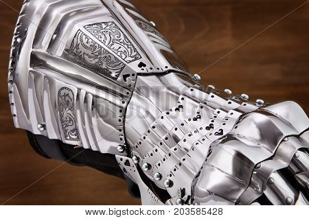 Medieval armor, detail of an ancient armor. Steel gloves on wooden background. bloody history