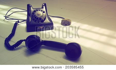 Background antique telephone black color and speaker at front Macro photo retro style focus select at the body Isolate on white wood floor has copy space.