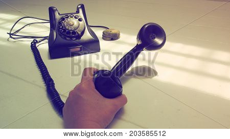 Antique telephone black color and speaker in my hand Isolate on white wood floor has copy space.