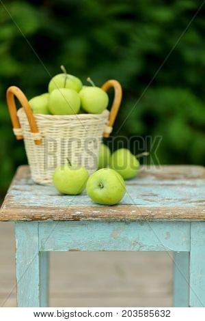 Homemade rustic green apples in a basket on an old stool. Selective focus.