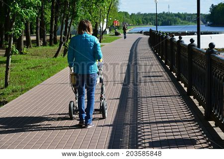 Khimki, Russia - May 30.2017. Women with a baby stroller on the embankment of the Moscow Canal