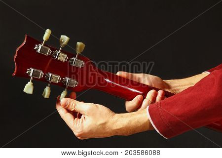 Rock guitarist tunes the guitar on a dark background