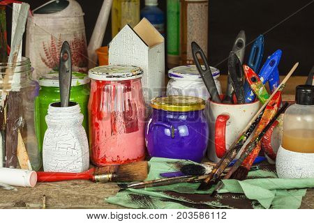 Decoupage products. Home Artist Workshop. Disorder on the work desk of the painter. Brushes and colors