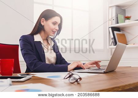 Business woman working on laptop at office. Businesswoman typing something on computer while sitting at her working place, copy space