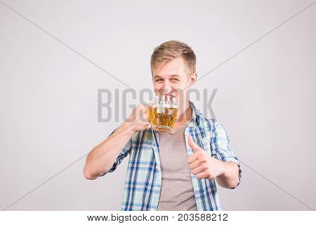Happy young man holding beer mug and showing thumbs up.