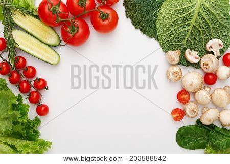 Border of fresh organic vegetables, fruits and nuts on white background. Healthy natural food on table with copy space. Cooking ingredients top view, mockup for recipe or menu