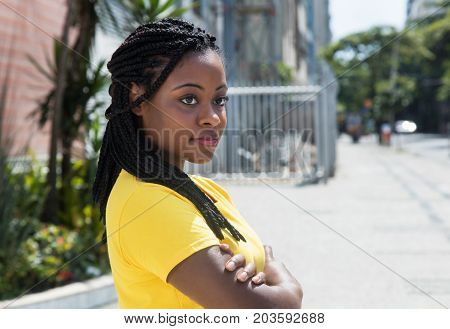 Smiling african american woman in yellow shirt looking sideways outdoor in the city in the summer