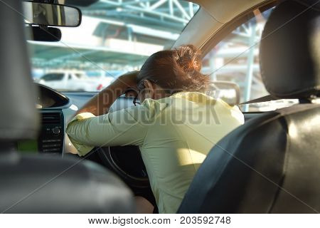 Rear view of Tired Asian Business woman sleeping while driving a car. Illness exhausted disease for overtime working concept.