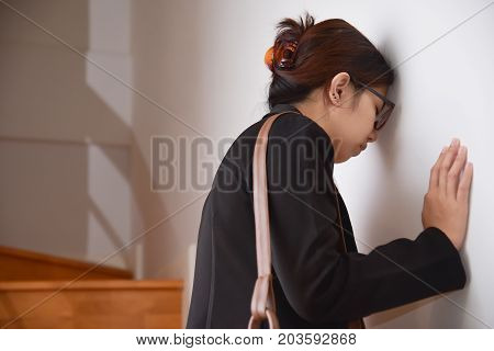 Exhausted Tired Asian Business Beautiful woman in black shirt standing on white wall. Stress from overtime working concept. Copy space.