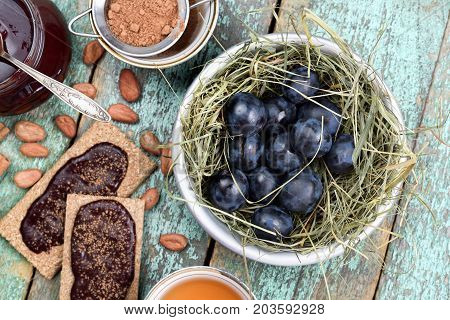 Raw organic plums in hay with homemade plum jam on healthy rye crackers and in glass jar above view