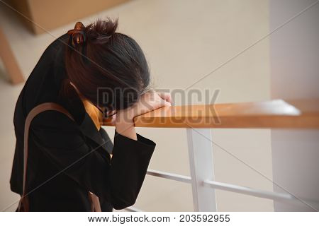 Exhausted Tired Asian Business Beautiful woman in black shirt standing and sleeping at stair. Stress from overtime working concept. Copy space.