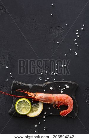 Boiled shrimp with salt and lemon on black background, copy space. Top view on appetizing seafood snack, restaurant serving.