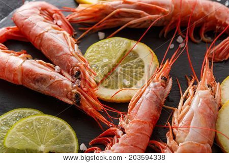 Boiled shrimps with lemon on black background, copy space. Close up of appetizing seafood snack, restaurant serving.