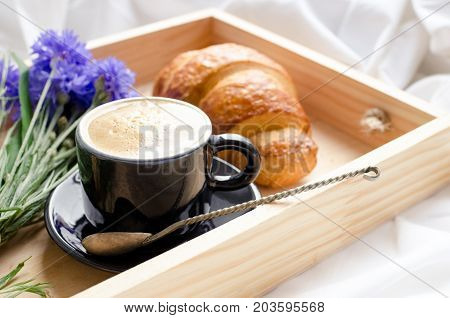 Romantic summer breakfast in bed tray with fresh croissant cup of coffee espresso with milk and bouquet of blue cornflowers. Good morning concept. Enjoy slow life. Traditional continental breakfast.