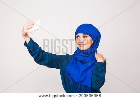 Portrait of beautiful muslim young woman wearing hijab take selfie using her mobile phone.