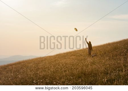 Happy woman enjoying the nature in vastness feel free and throwing her hat in the air toward the setting sun. Lifestyle and celebration concept.