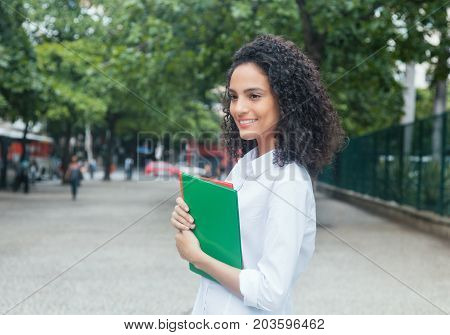 Cute latin female student with curly hair and white shirt outdoor in the city