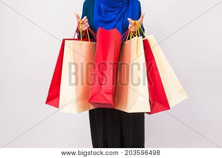 Close up of muslim woman with shopping bag on white background.