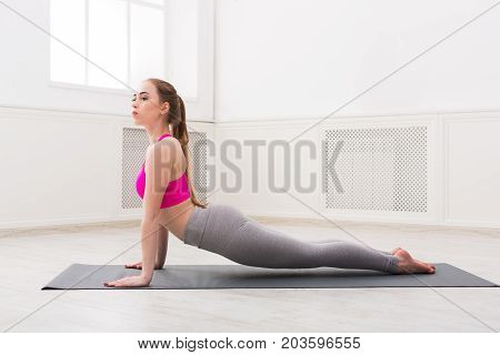 Fitness, woman training yoga in cobra pose in gym at white background, copy space. Young slim girl makes exercise.