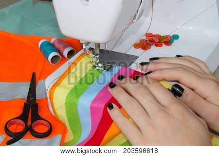 seamstress sews clothes. Workplace of tailor - sewing machine rolls of thread fabric scissors. sewing machine and female scissors