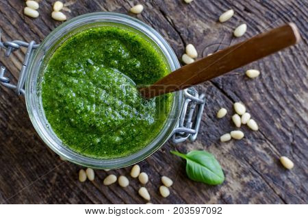 Pesto genovese - traditional Italian green basil sauce with pine nuts on rustic wooden background. Top view.