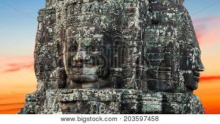 Stone smiling face in Prasat Bayon part of Angkor Khmer temple complex among tourists ancient landmark and place of worship in Southeast Asia Siem Reap Cambodia