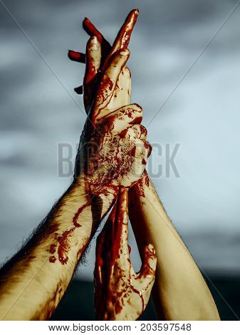 Halloween bloody hands on grey sky background. Vampire hands with red blood stretching up. Maniac or murderer concept. Halloween holiday celebration