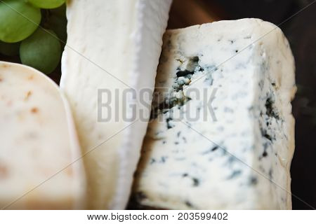 Cheese assortment background. Blue cheese, brie and hard goat cheese with herbs as pieces and grapes. Focus on blue cheese. Still life, closeup, selective focus