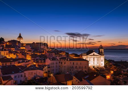 View of the Alfama neighborhood from the Portas do Sol viewpoint at sunrise in Lisbon Portugal; Concept for travel in Portugal